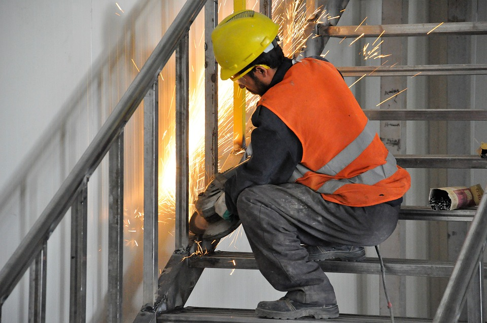 Metal worker working on stairs